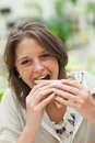 Female student eating sandwich in the cafeteria close up portrait of a smiling Royalty Free Stock Image