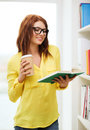 Female student in eyeglasses with book and coffee education concept smiling redhead takeaway library Stock Photo