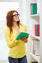 Female student in eyeglasses with textbook education concept smiling redhead library Stock Images