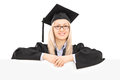 Female student in graduation gown posing behind blank panel Stock Image