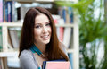 Female student keeps books young with at the library research studying Stock Photos