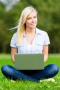 Female student with laptop sitting on the grass attractive silver green in summer park Royalty Free Stock Image