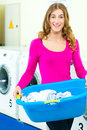 Female student in a laundry young woman with basket laundrette she washed their clean and is happy about it Stock Photo