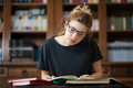 Female student in a library reading on a desktop Royalty Free Stock Photo
