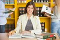 Female student with pencil and books at college portrait of happy while friends in background library Royalty Free Stock Photo