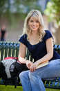 Female student sitting on bench portrait of young at college campus Royalty Free Stock Images