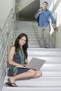 Female Student Sitting While Man Walking Down Stairs Royalty Free Stock Images