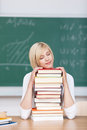 Female student sleeping on stacked books young at desk in classroom Royalty Free Stock Photo