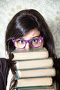 Female student stress studying woman young overwhelmed holding a pile of old books girl with glasses looking upset Royalty Free Stock Photography