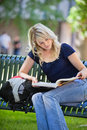 Female student studying young college sitting on bench and reading book Stock Photo