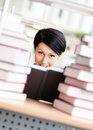 Female student is surrounded with piles of books Stock Photo