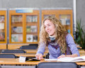 Female student with tablet computer in library looking away Royalty Free Stock Images