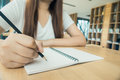 Female student taking notes from a book at library. Young asian woman sitting at table doing assignments in college library. Royalty Free Stock Photo