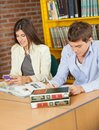Female student using mobilephone while friend young studying in university library Royalty Free Stock Photography