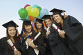 Female students with diplomas and balloons standing against sky portrait of happy Royalty Free Stock Photos