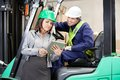 Female supervisor and forklift driver using digital tablet at warehouse Royalty Free Stock Image