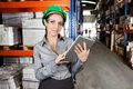 Female supervisor using digital tablet at portrait of young with protective eyeglasses warehouse Stock Images