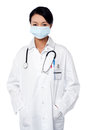 Female surgeon posing with hands in lab coat young wearing a face mask Royalty Free Stock Images