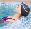 Female swimmer in blue water swimming pool sport woman portrait of a wearing a cap and goggles Stock Image