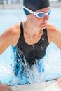 Female swimmer exiting pool with black swimsuit and cap lifting herself out of swimming Stock Photos