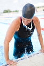 Female swimmer exiting pool with black swimsuit and goggles around neck lifting herself out of swimming Stock Photos
