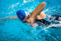 Female swimmer in an indoor swimming pool - doing crawl Royalty Free Stock Photo