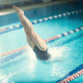 Female swimmer, that jumping into indoor swimming pool. Royalty Free Stock Photo