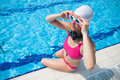 Female swimmer at pool edge freediver with neck weight preparing for dive of outdoor swimming Stock Images