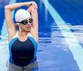 Female swimmer stretching before workout at the pool Royalty Free Stock Photos