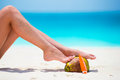 Female tanned smooth legs with suncream and coconut on white beach Royalty Free Stock Photo
