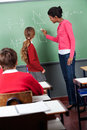 Female teacher teaching mathematics to students side view of young in classroom Stock Images