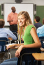 Female teenage pupil in classroom holding pencil smiling to camera Royalty Free Stock Photo
