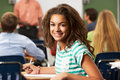 Female teenage pupil in classroom smiling at camera Royalty Free Stock Image
