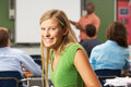 Female teenage pupil in classroom smiling at camera sitting down Stock Image