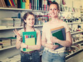 Female teenager with mother are choosing pen and notebook