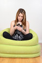 Female teenager using cell phone sitting in green bean bag chair Royalty Free Stock Image