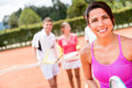 Female tennis player with a group of friends at the court Royalty Free Stock Photo