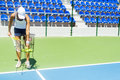 Female tennis player practicing service with the ball basket being at hand Royalty Free Stock Image