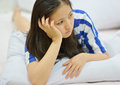 Female thinking while lying on the bed at home Royalty Free Stock Photography