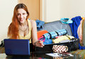Female tourist buying tickets online or reserving hotel in the internet using laptop Stock Images