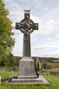 Female tourist at irish memorial celtic cross in honor of saint colomba founder of the colomban monks Royalty Free Stock Photo