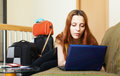 Female tourist reserving hotel online in internet using laptop at home Royalty Free Stock Image