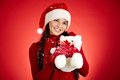 Female with toy joyful girl in santa cap white teddy bear over red background Stock Image
