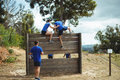 Female trainer assisting fit man to climb over wooden wall during obstacle course
