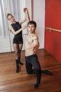 Female trainer assisting male ballet dancer full length of in studio Stock Images