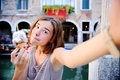 Female traveler making selfie photo with traditional italian ice cream in Venice