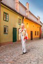 Female traveler walks around Golden Lane, Prague, Czech Republic.