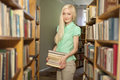 Female university student holding books in library Royalty Free Stock Images