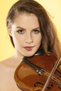 Female violinist a beautiful over a yellow background Royalty Free Stock Photo