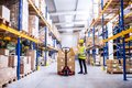 Female warehouse worker loading or unloading boxes. Royalty Free Stock Photo